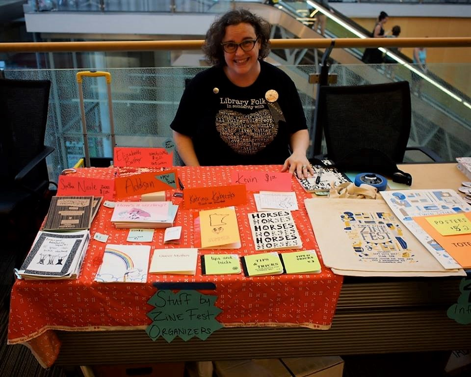 Violet sitting at a table full of zines at the 2018 Twin Cities Zine Fest