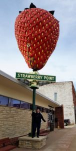 Violet standing underneath a ten foot strawberry statue on top of a twelve foot pole. Underneath the strawberry is a sign reading Strawberry Point, Iowa