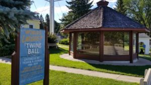 photo of the glassed-in enclosure of the world's largest ball of twine, along with a faded sign discussing the creation of the twine ball and measurements